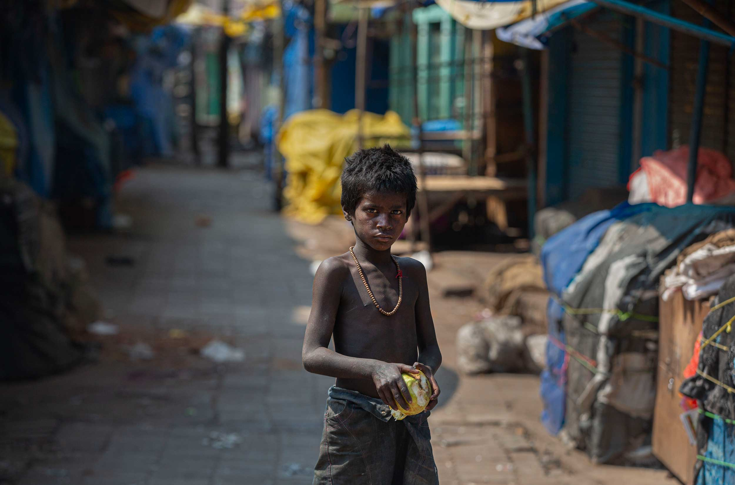 A homeless boy collects rotten fruits from a deserted market during the Covid-19 lockdown in Guwahati on Wednesday.