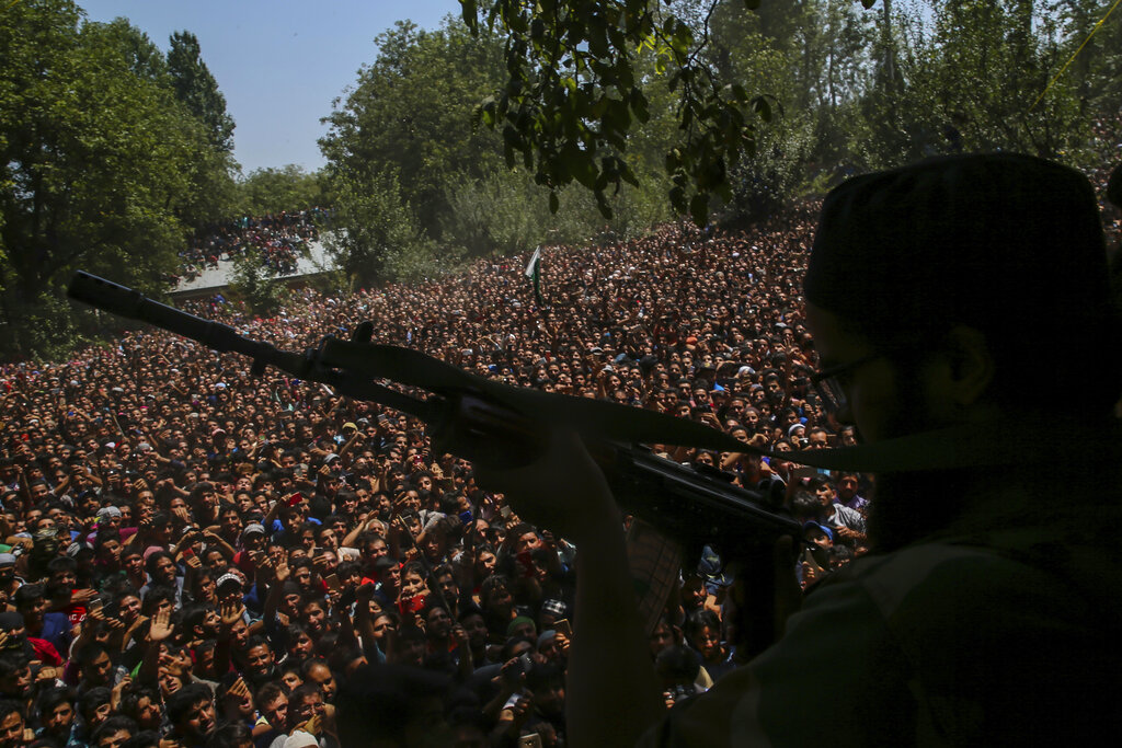 In this Aug. 4, 2018, file photo, a Kashmiri rebel fires his gun to salute fallen comrades during their joint funeral in Malikgund village, south of Srinagar, Kashmir