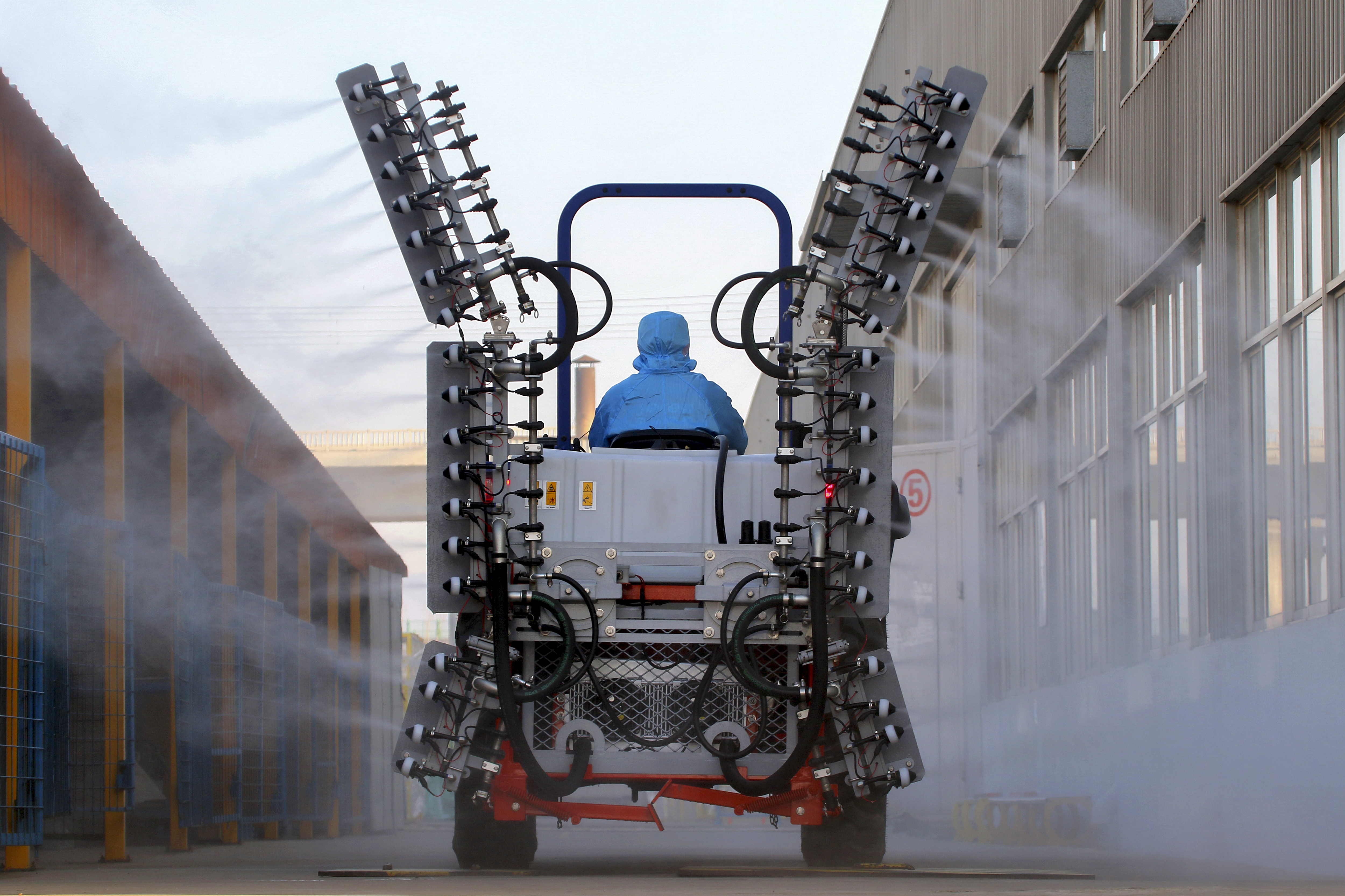 A worker in a tractor operates electrostatic spray to disinfect a workplace following the coronavirus outbreak, in Yantai city in east China's Shandong province, on Sunday.