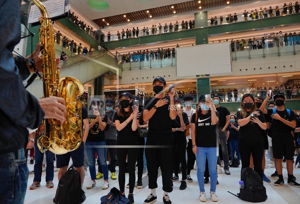 Protesters wear masks in defiance of a recently imposed ban on face coverings perform at a shopping mall in Hong Kong on October 13, 2019.