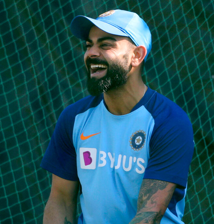 India's captain Virat Kohli laughs as he gets ready for a practice session ahead of the second one-day international cricket match between India and Australia in Rajkot on Thursday