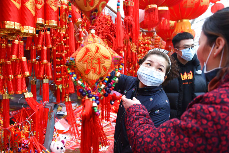 People wear face masks as they shop for decorations for the upcoming Lunar New Year at a market in Fuyang in central China