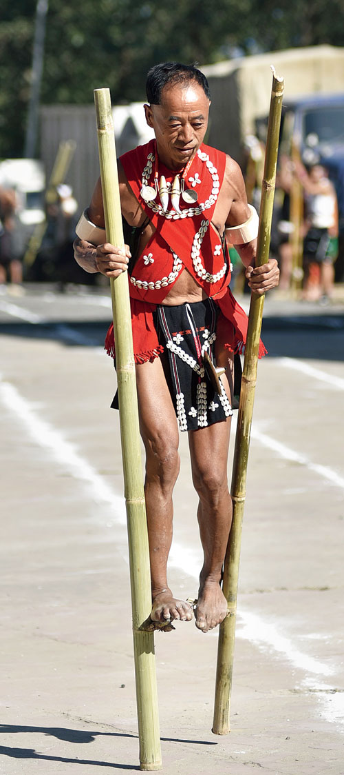 A man in traditional Naga attire, captured midway during his race on stilts