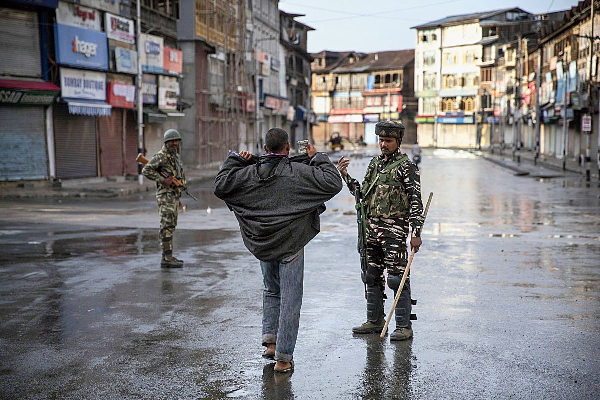A paramilitary soldier orders a Kashmiri to open his jacket before frisking him during curfew in Srinagar on August 8, 2019.