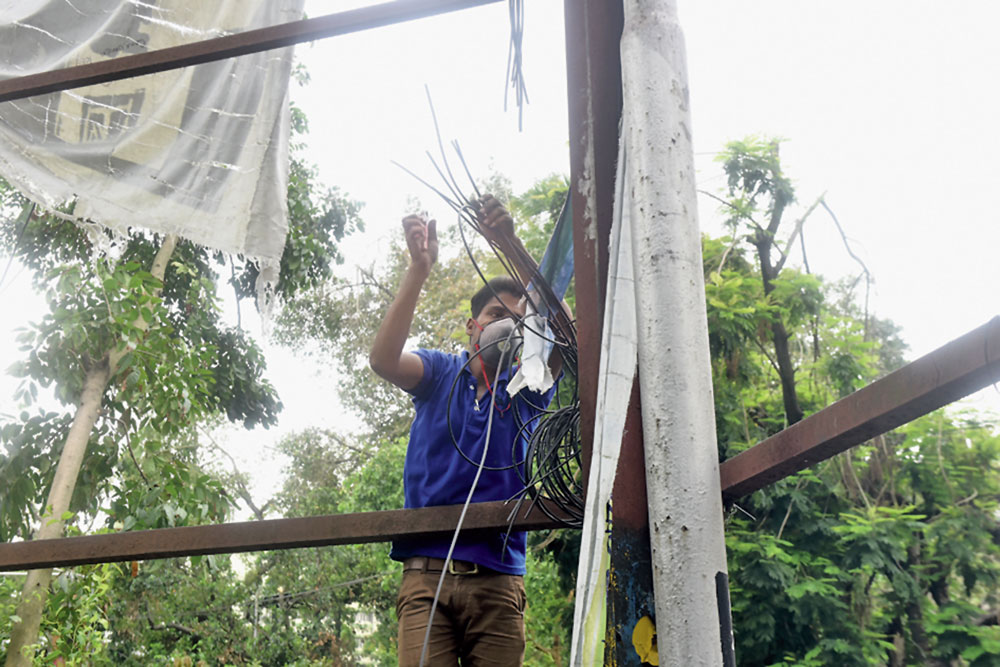 A CMC worker cuts hanging cables at Alipore on Saturday.
