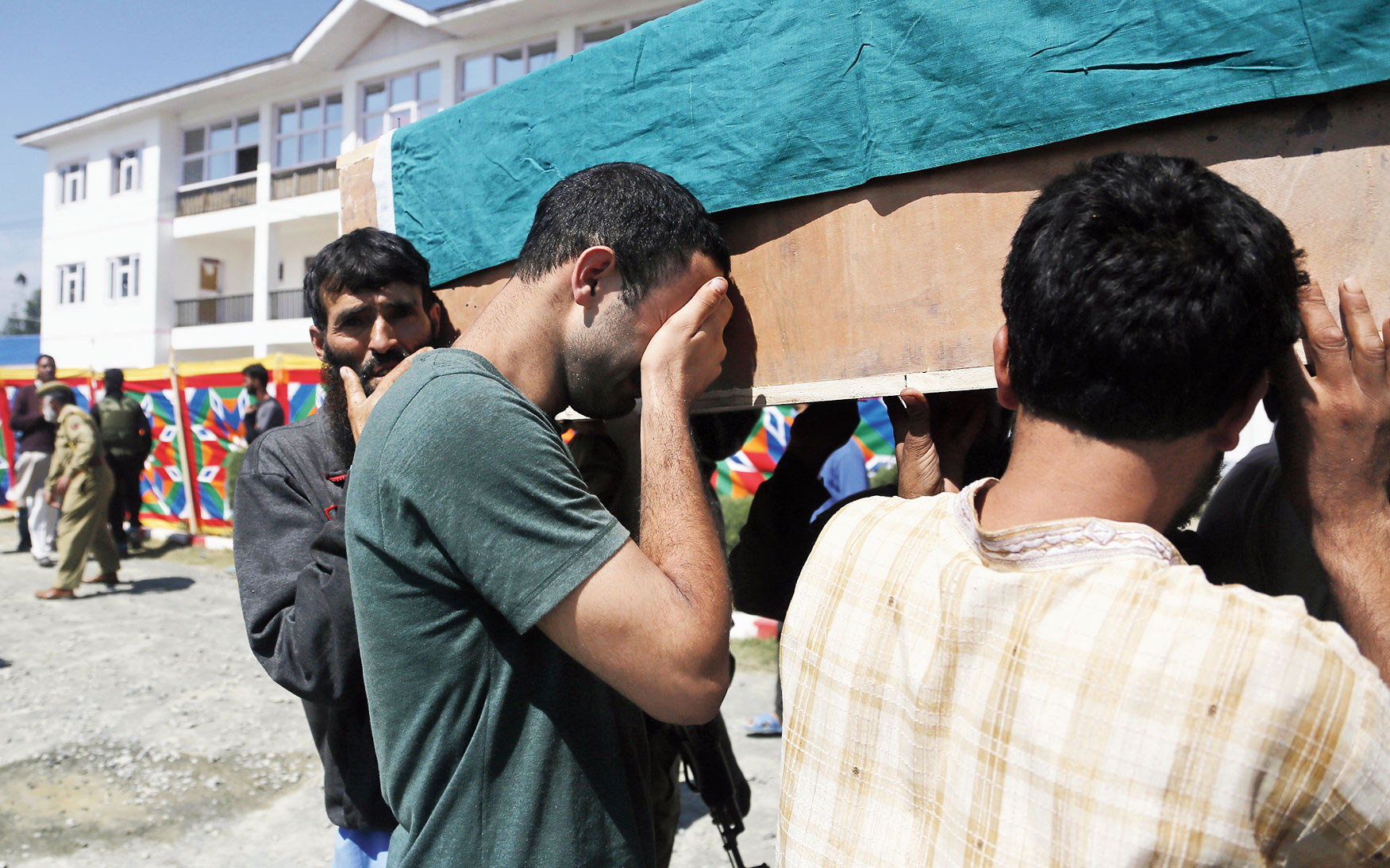 A family member of a slain policeman cries as he carries the coffin in Shopian on Friday.