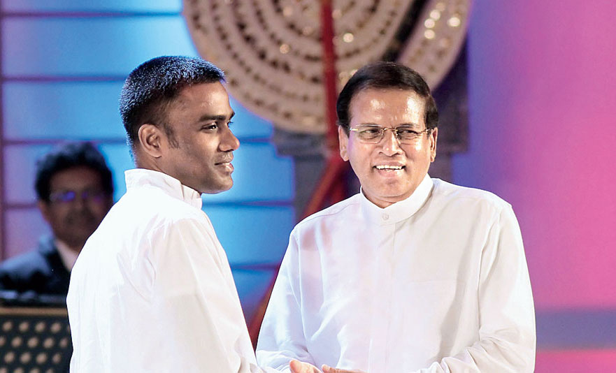 File picture of Sri Lankan president Maithripala Sirisena (right) holding the hands of a former Tamil Tiger insurgent, Sivaraja Jenivan, after pardoning him during a function to mark the first anniversary of his election to the prime minister's office in Colombo on January 8, 2016