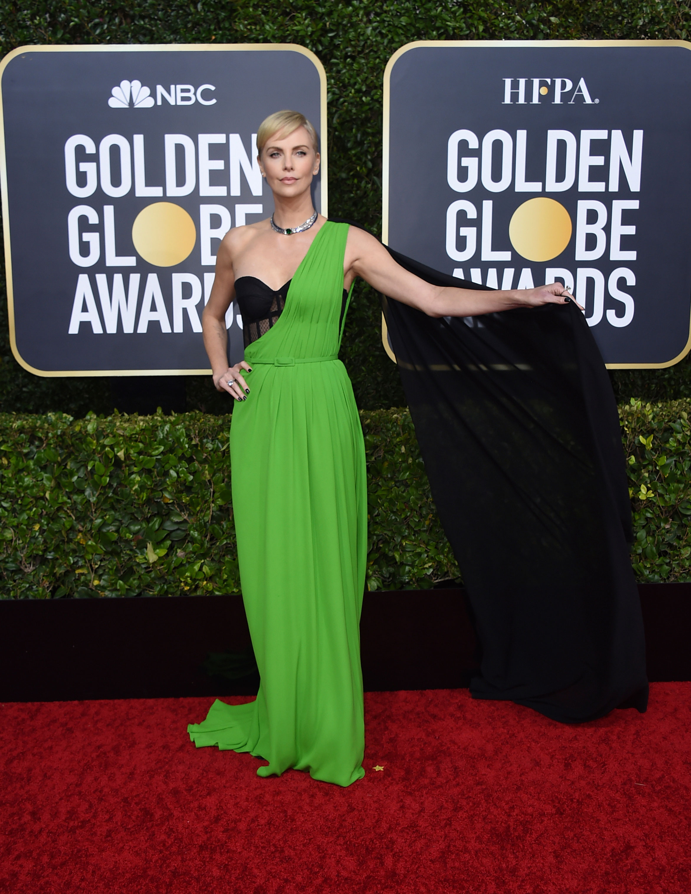 Charlize Theron's minimalist look made us go 'wow'! At 44, the Bombshell actress slayed in a one-shoulder green Dior gown with a flowy black cape that she wore with a lacy black corset and a tiny belt in the same green shade accentuating her tiny waist.