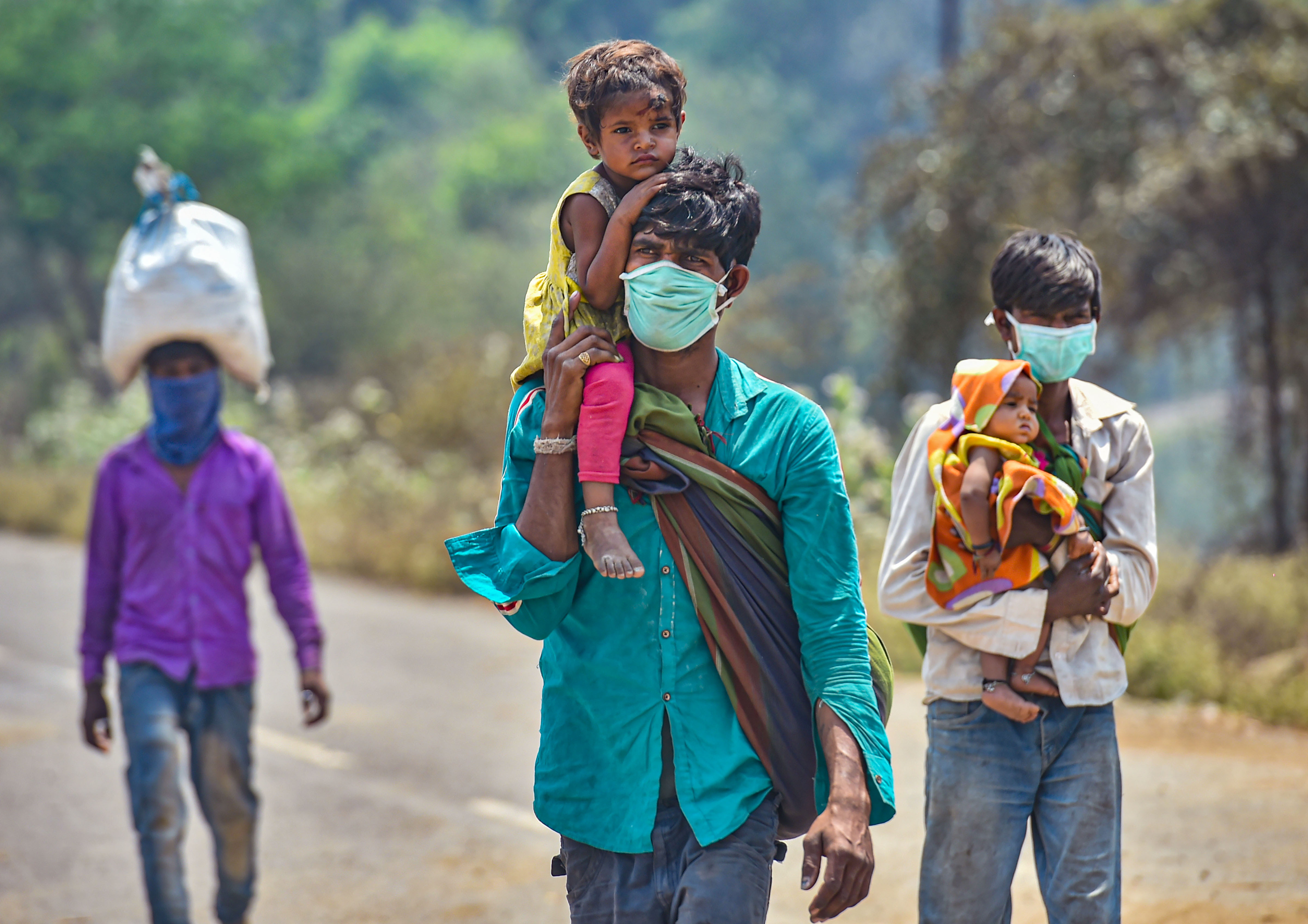 Migrant workers from Madhya Pradesh walk along the Mumbai-Ahmedabad highway, following the coronavirus lockdown, in Palghar, Monday, March 30, 2020.