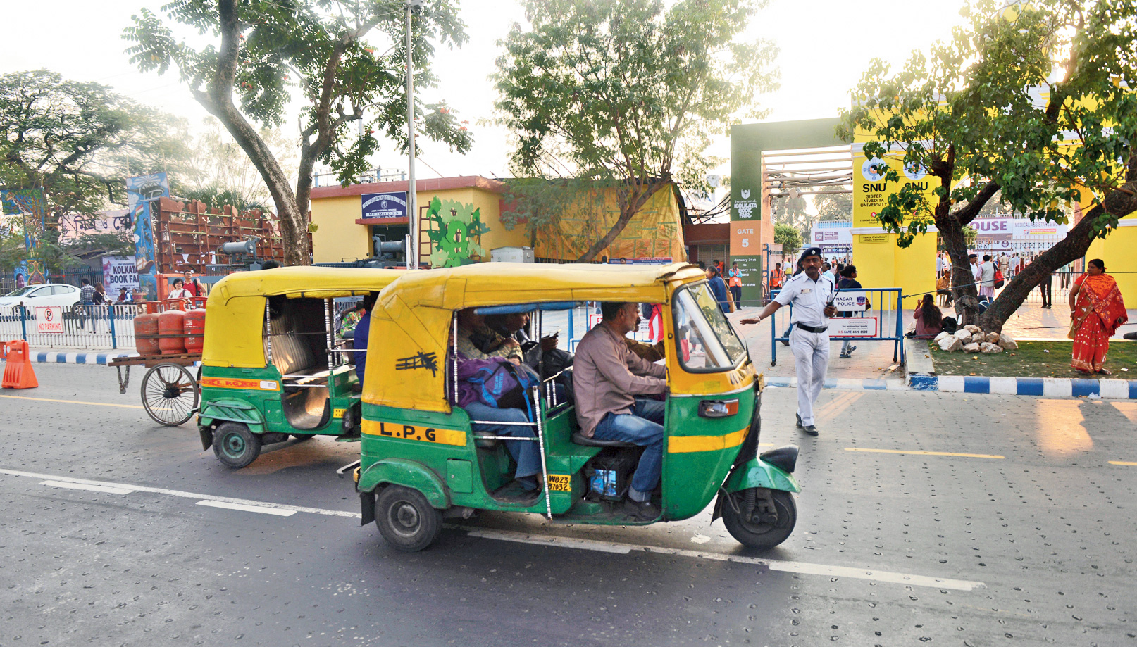 Autorickshaws pass by Central Park, where the Calcutta Book Fair is being held, on Tuesday afternoon.