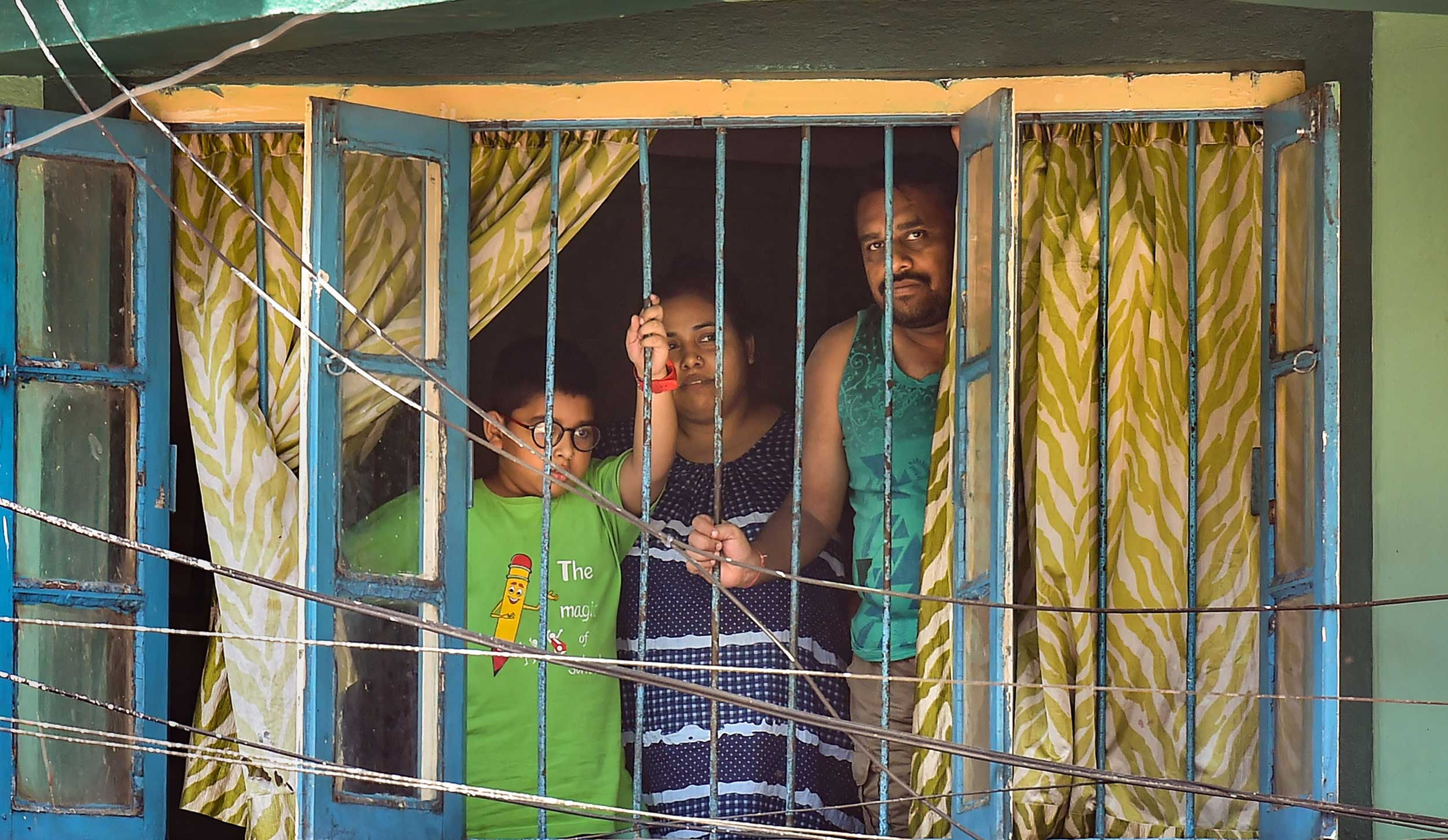 A family looks out of their window during the nationwide lockdown in Calcutta on Tuesday.