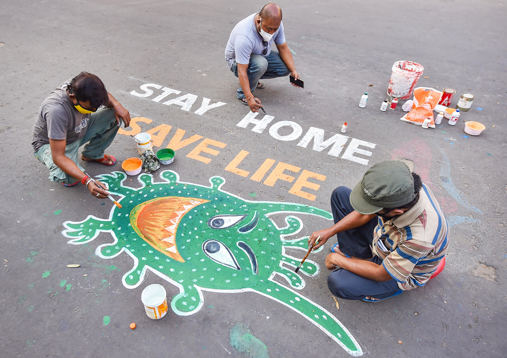 Artists paint graffiti on a road to raise awareness about the COVID-19 during nationwide lockdown imposed to contain the coronavirus pandemic, in Calcutta, Thursday, April 9, 2020.