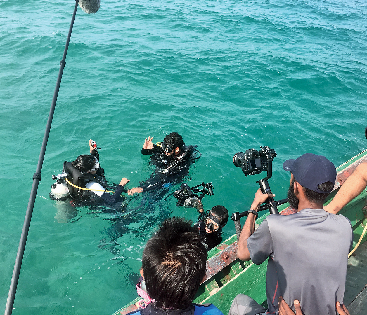 The film crew interviews Mohammed Hussain (gesturing with his right hand) in the Andamans water.