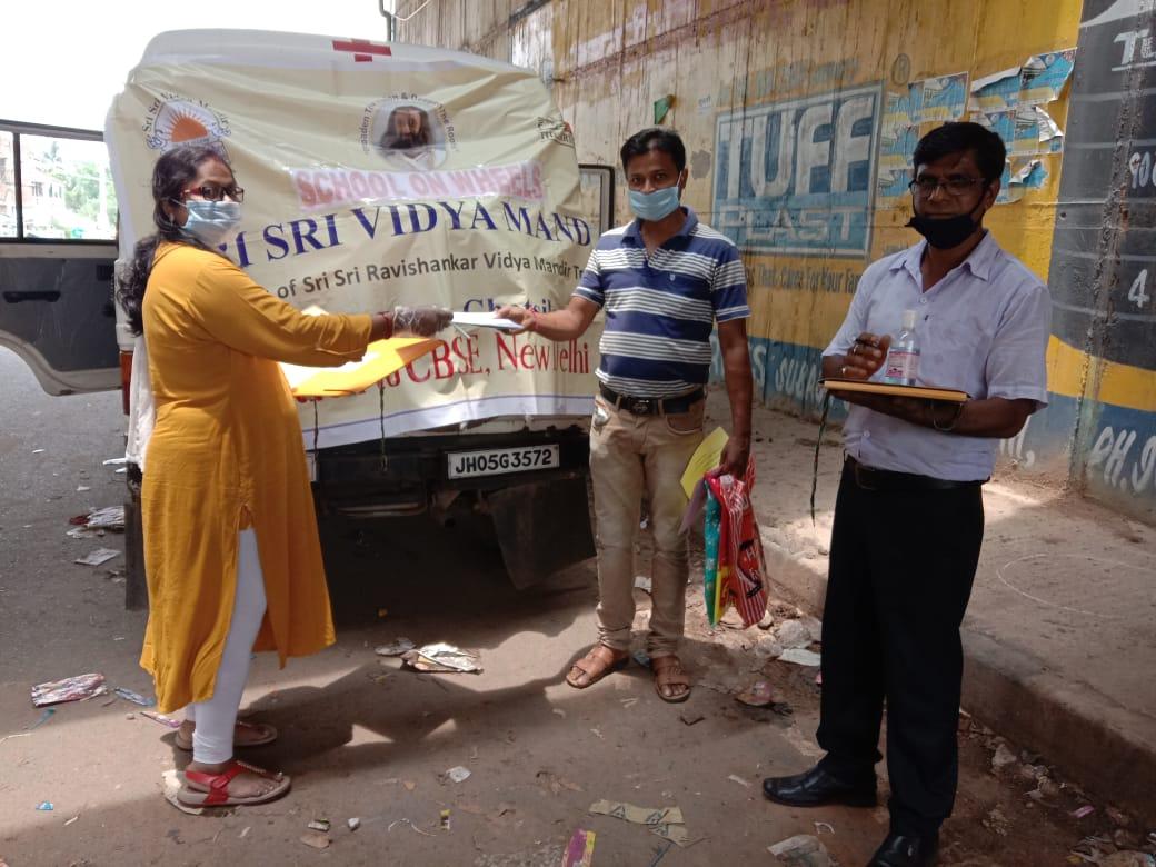 Parents collect worksheets from teachers of Sri Sri Vidya Mandir at Ghatshila