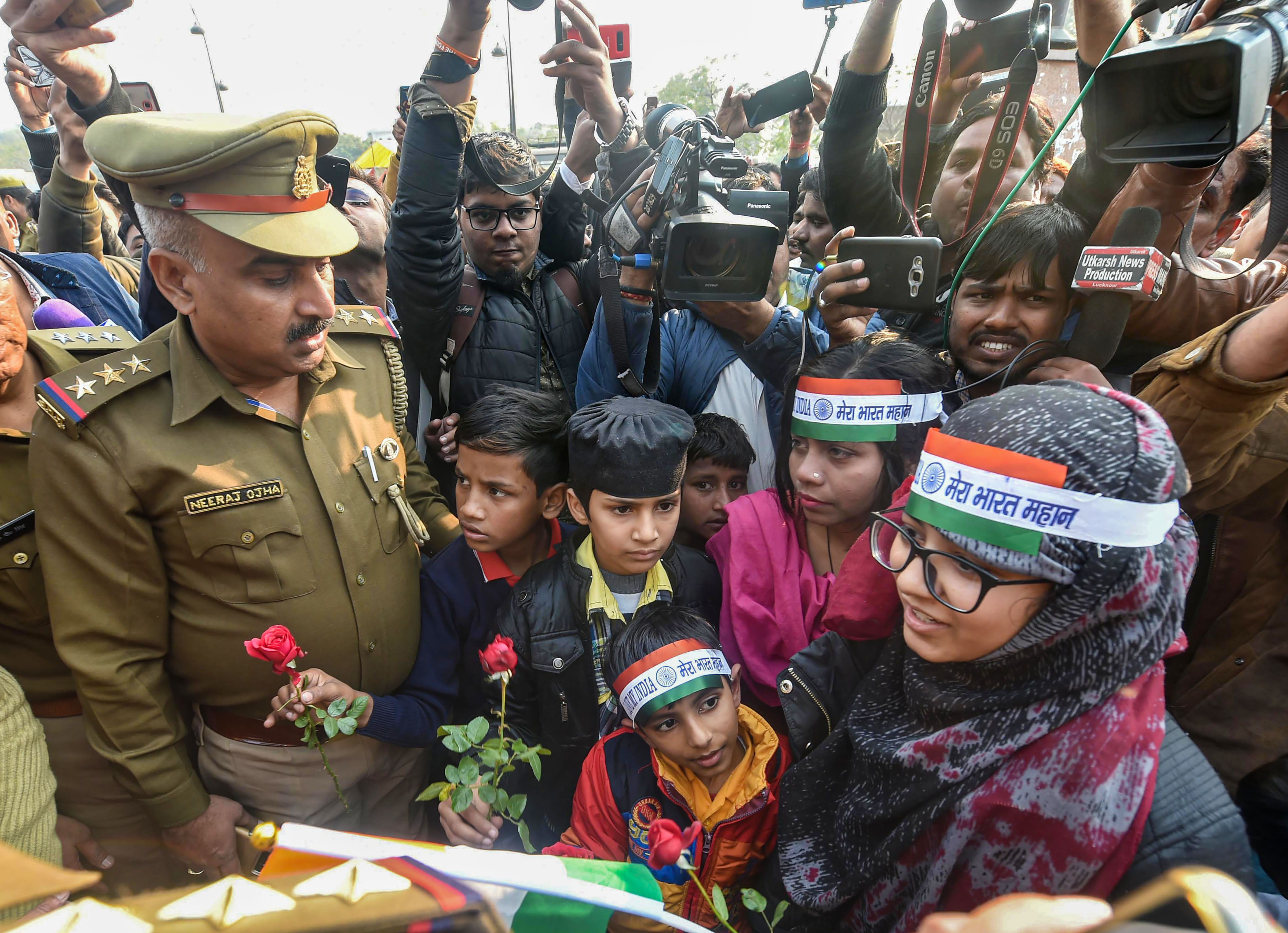 Women protesters along with their children offer roses to policemen during a peaceful dharna against CAA and NRC, at the historic Clock Tower in Lucknow, Saturday, January 25, 2020.