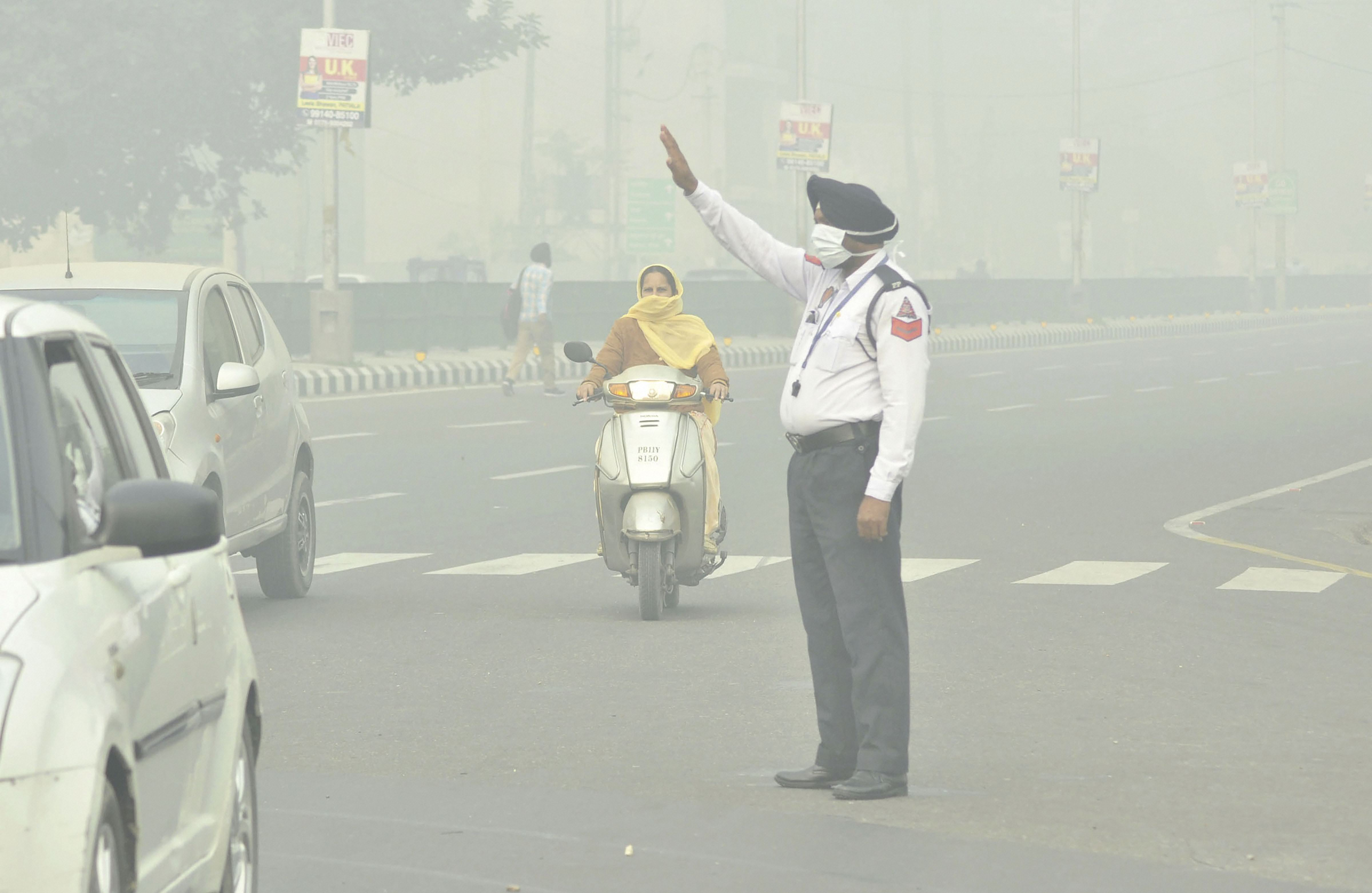 A policeman wears a mask as he manages traffic amid heavy smog, in Patiala, Sunday, November 3, 2019.