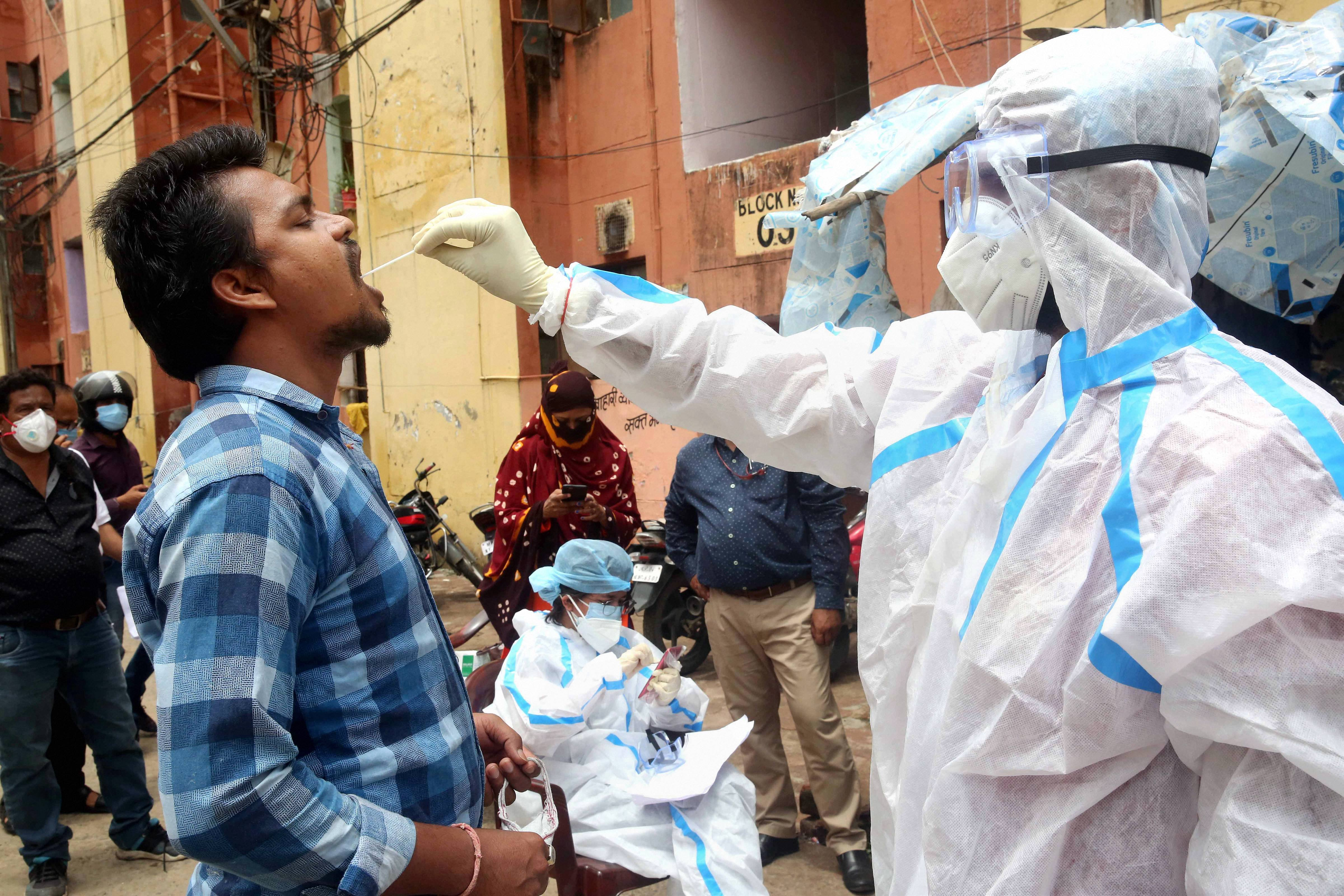 A medic collects swab samples from a man as part of a state-wide door-to-door Kill Corona campaign to curb the spread of the coronavirus in Bhopal on Saturday