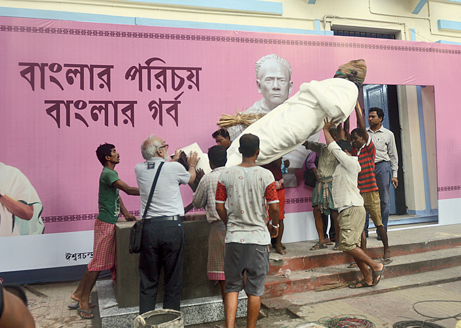 Gautam Pal (second from left) helps install the fibre glass statue at Vidyasagar College on Monday.