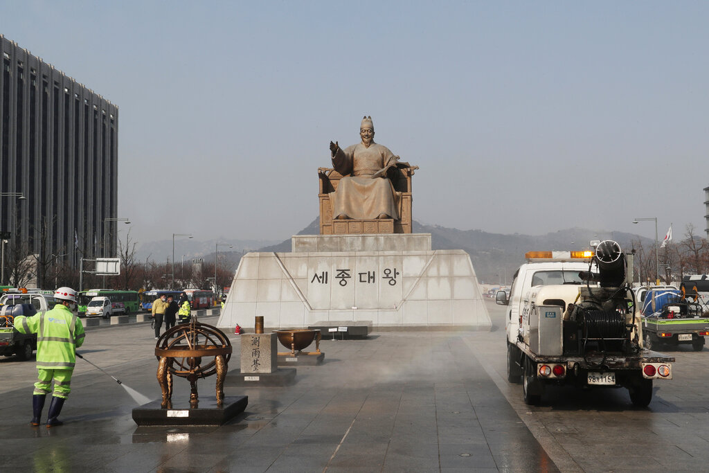 A worker and vehicle spray disinfectant and water as a precaution against the new coronavirus in front of the statue of King Sejong in the Joseon Dynasty, at the Gwanghwamun Plaza in Seoul
