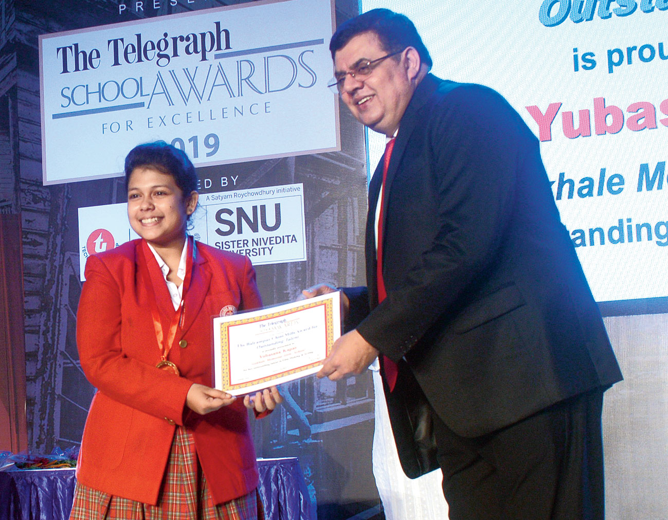 Yubasana Kapas receives the The Balrampur Chini Mills Award for Outstanding Talent from Barry O'Brien, trustee of The Telegraph Education Foundation.