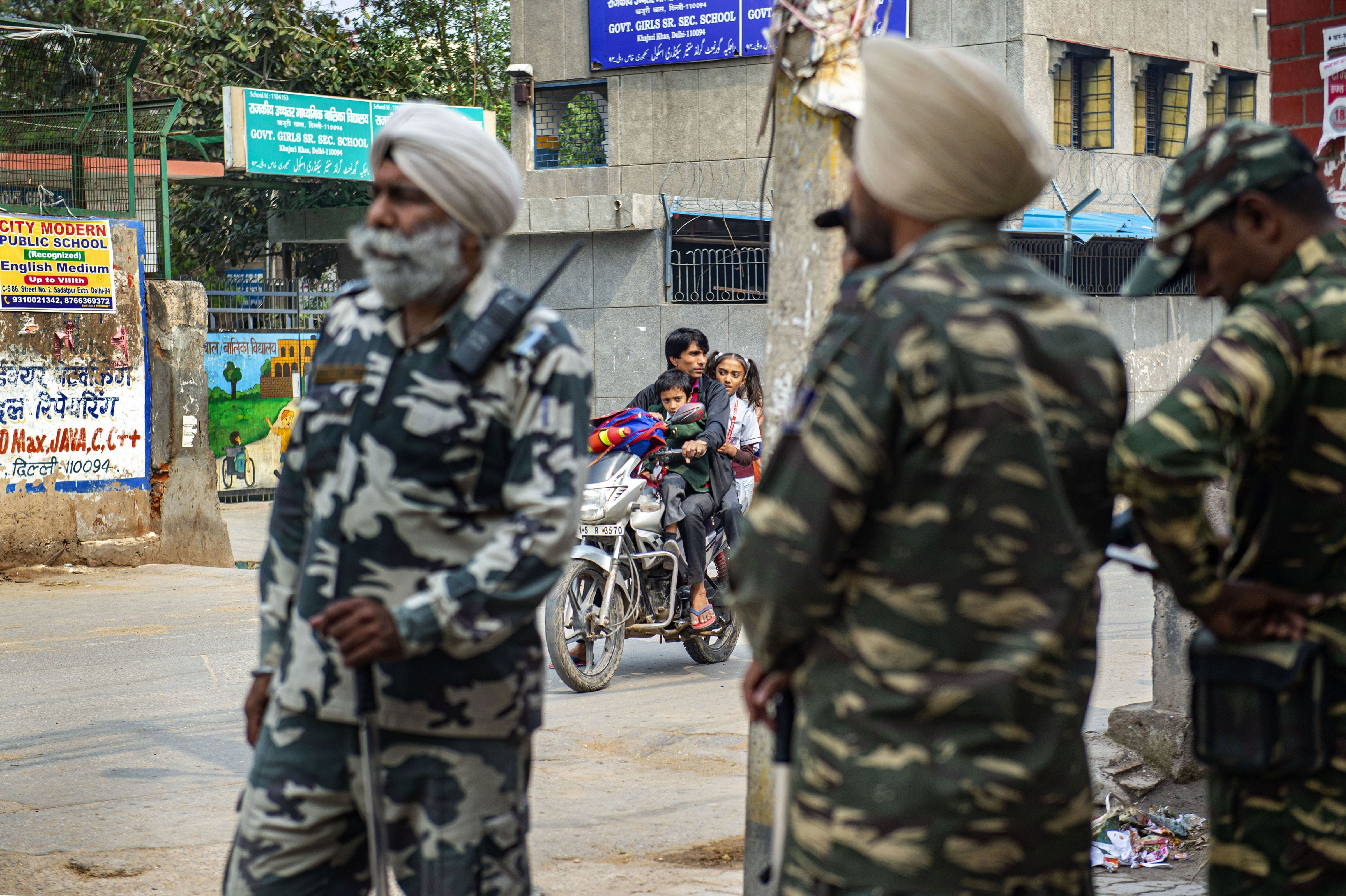 Security personnel stand guard along a road as children return from school at riot-affected Khajoori Khas area of northeast Delhi, Monday, March 2, 2020