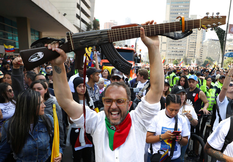 A Colombian musician holds up his 'escopetarra', a guitar that incorporates an assault rifle as a symbol of peace, during a musical protest against the government of President Ivan Duque in Bogota, Colombia, on December 8