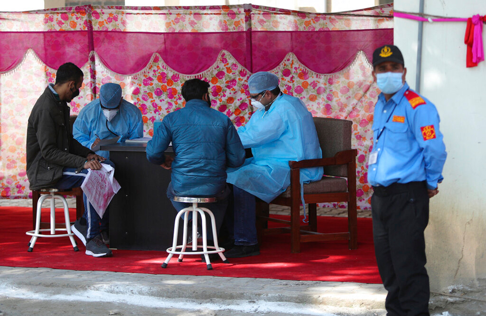 Doctors examine people with flu-like symptoms in Jammu on March 19