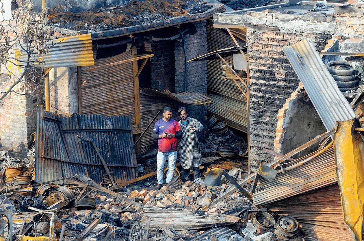 Shop owners look at the charred remains of the tyre market in the riot-affected Gokulpuri area of northeast Delhi.