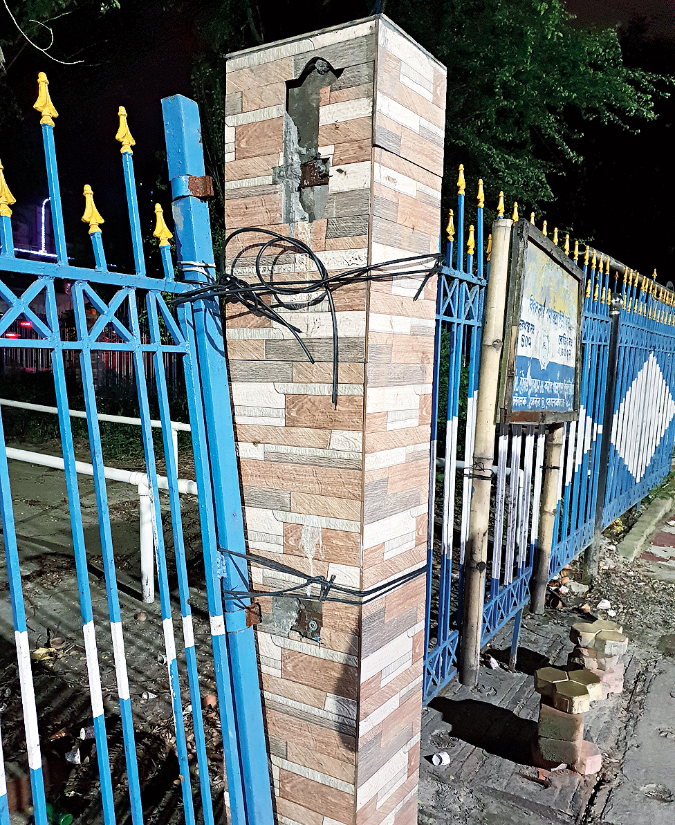 A broken gate of the canal-side park tied to a pillar.