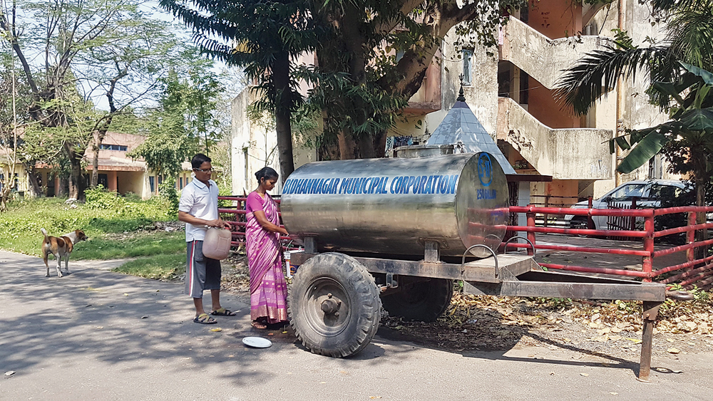 Residents queue up for water from a tanker sent by the corporation on Sunday