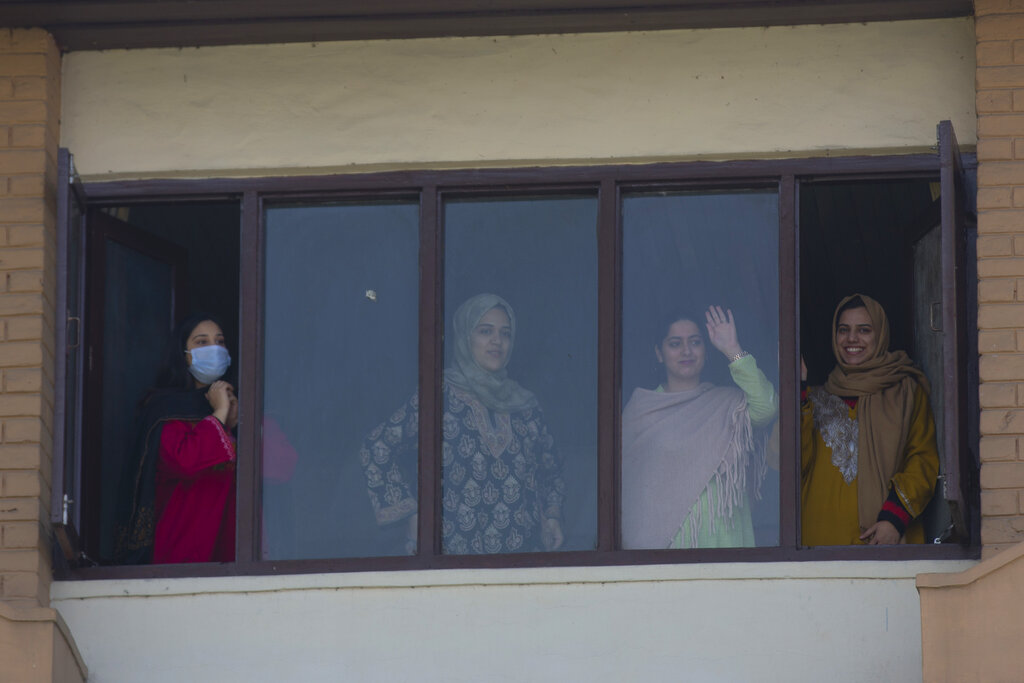 A Kashmiri medical student, who has completed her quarantine period after returning from Bangladesh, waves from her hotel room before being released in Srinagar, on Friday, April 3, 2020.