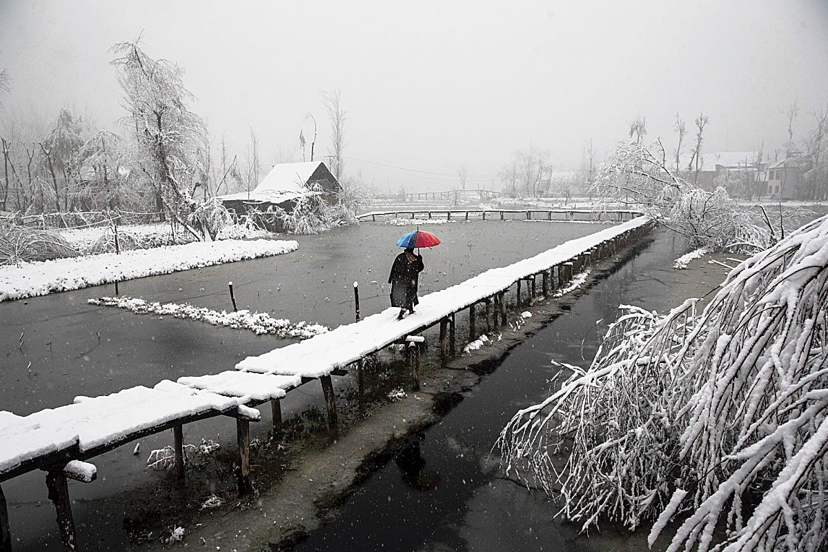 A Kashmiri walks on a snow-covered footbridge as it snows in the interiors of Dal Lake in Srinagar on December 13, 2019.
