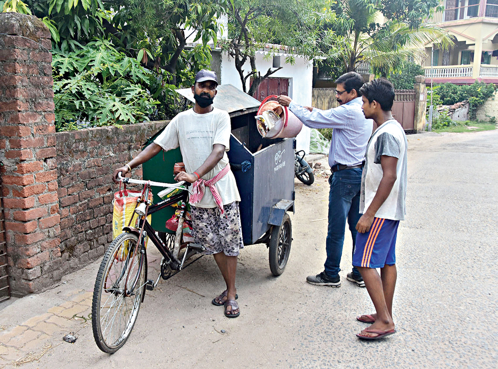 A Bekar Bandh resident in Dhanbad hands over trash to sanitation workers on Tuesday
