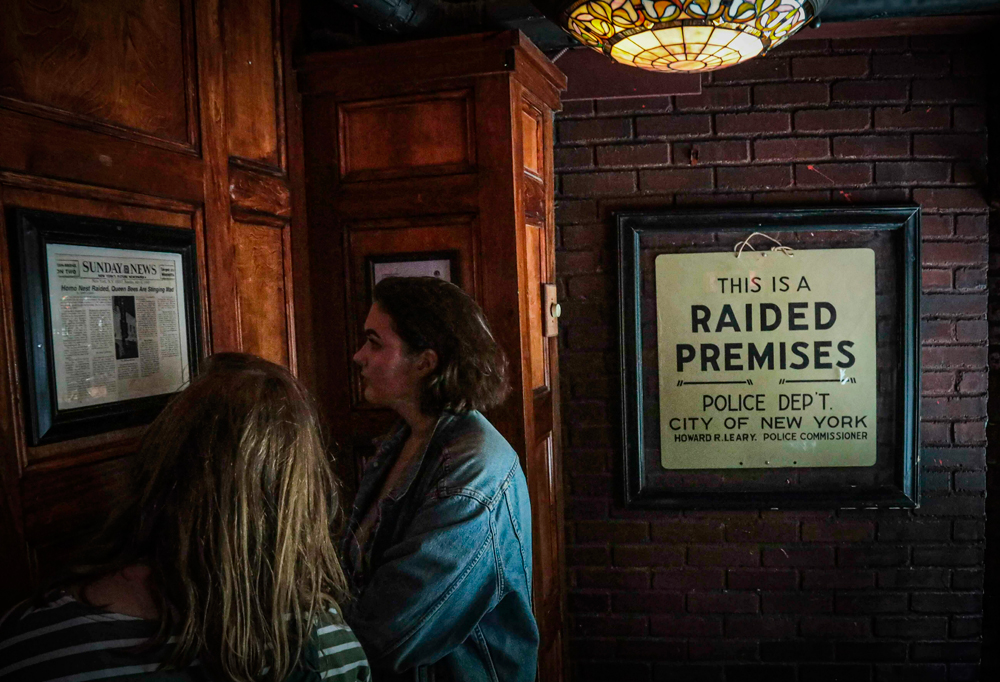 Stonewall Inn visitors read news clipping headlining the 1969 riots that followed a police raid of the bar in New York