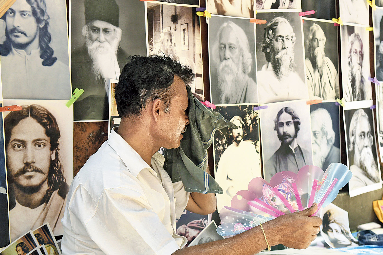 A hawker selling Rabindranath Tagore's portraits fans himself and wipes sweat off his face near Jorasanko Thakurbari on the poet's birth anniversary on Thursday.