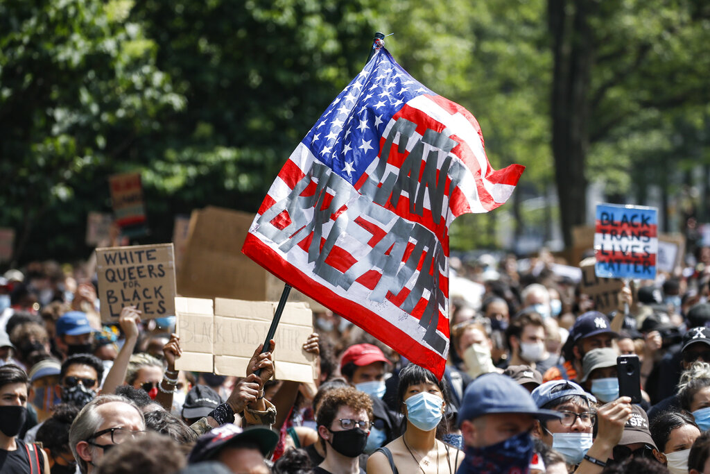 A protester waves an American flag with a message that reads