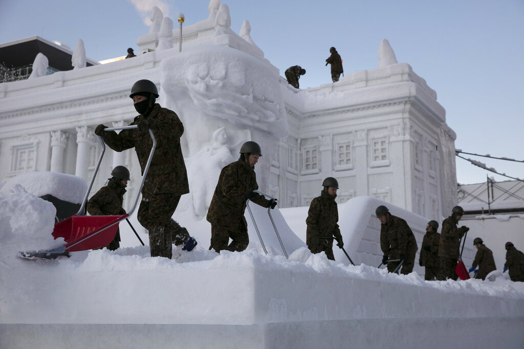 Self-Defense Force members remove fresh snow piled on a large snow sculpture of Poland's Palace on the Isle during the Sapporo Snow Festival at Odori Park in Sapporo