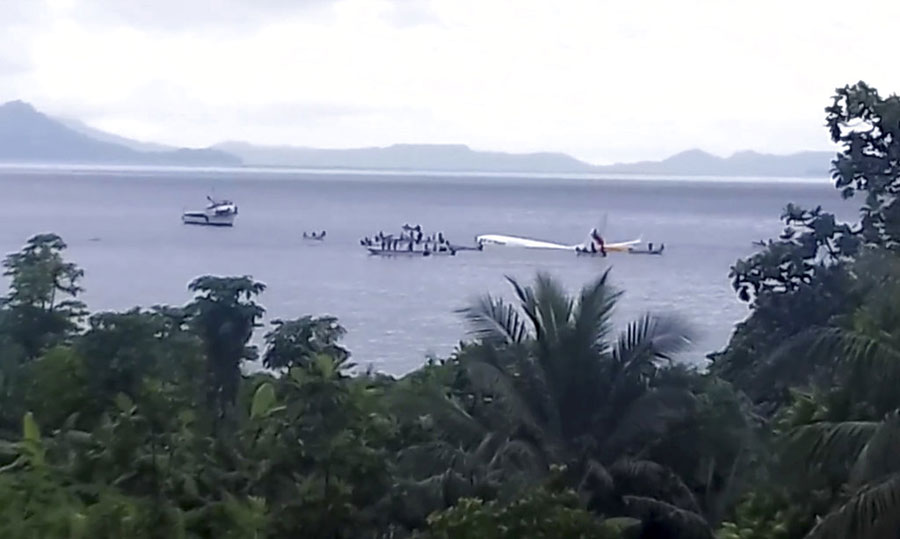 Air Niugini plane floating in the Pacific lagoon on Friday.