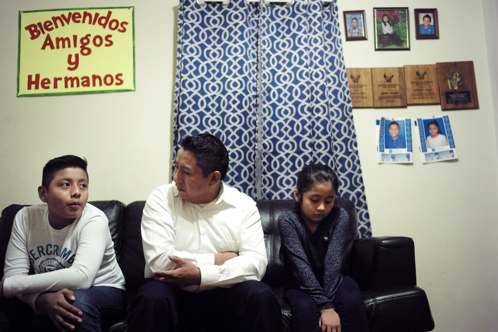 Audencio Lopez (center) who crossed the border illegally as a teenager in 1997, is seated with two of his children, Anaias, 12 (left) and Mercy, 8, during an interview with The Associated Press, at their home in Lynn, Massachusetts.