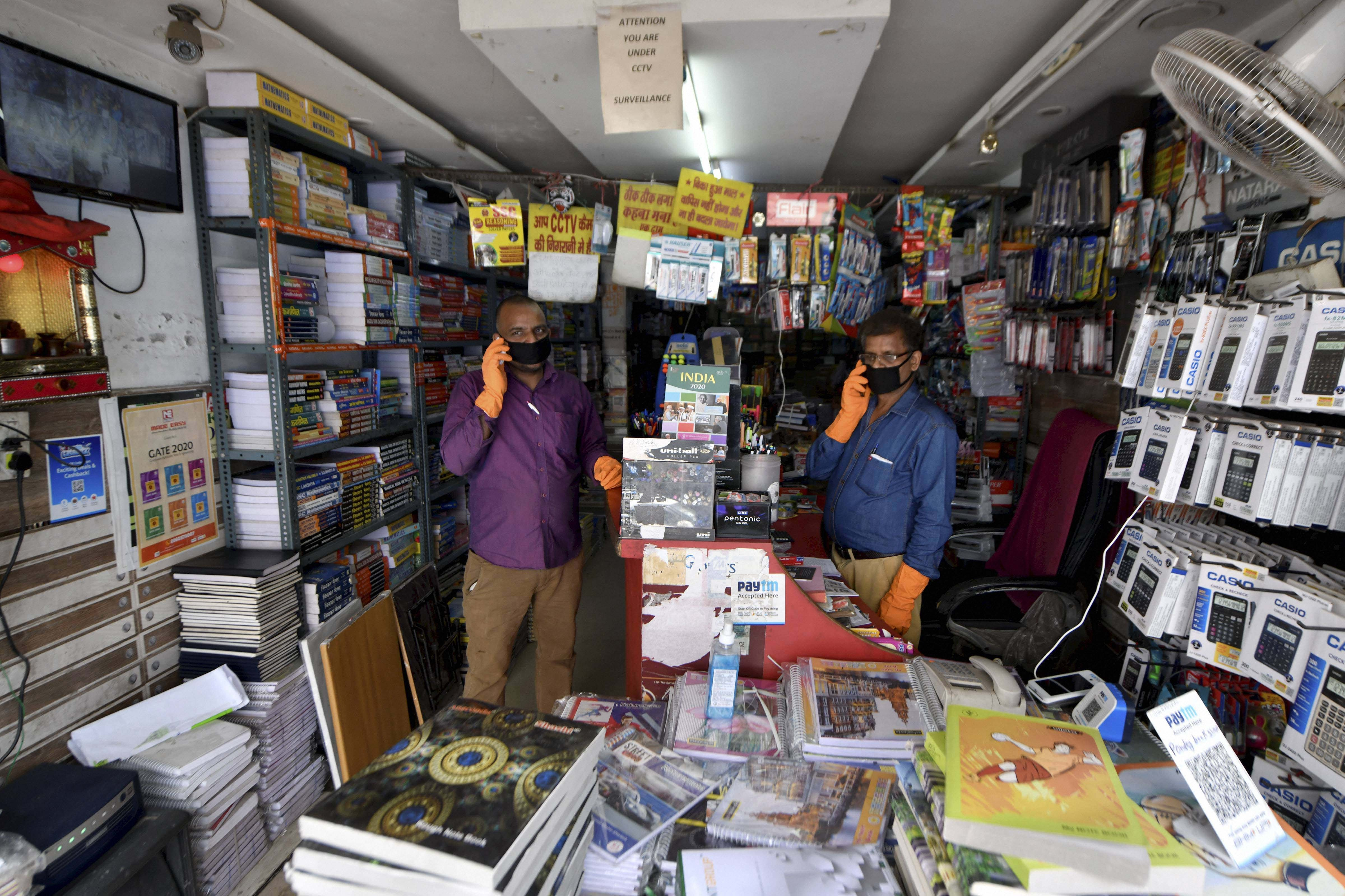 Shopkeepers wait for customers at a bookstore after authorities eased the lockdown restrictions at Laxmi Nagar in New Delhi on April 25, 2020.