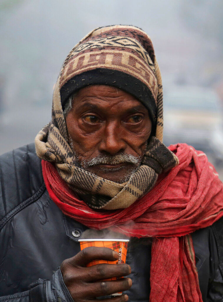 A man holds a hot cup of tea on a cold and foggy morning in Jammu on December 31, 2019.