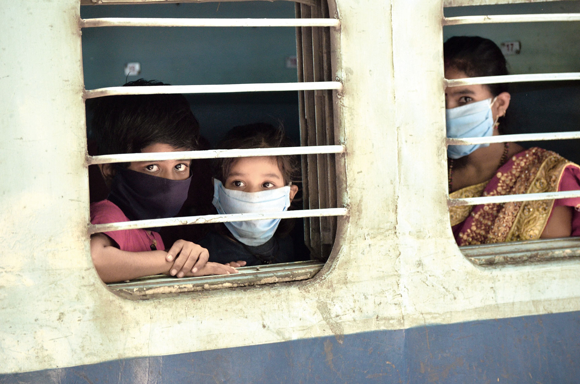 Looking beyond: Two children and a woman peep out of the window as a train reaches Dhanbad station from Lingampally in Telangana on Friday.