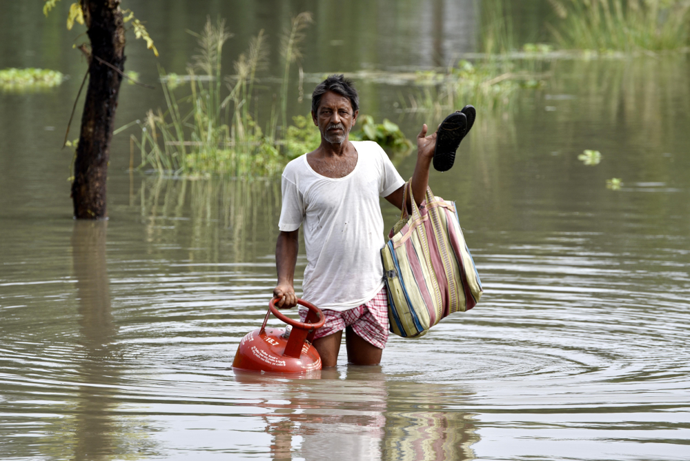A man carries a cooking gas cylinder and other items through flood water in Jania village in Barpeta, Assam, in this July 12, 2019 picture. Flood management needs to focus not only on flood defence strategies but also on flood risk preparation, mitigation, protection, and post-flood recovery