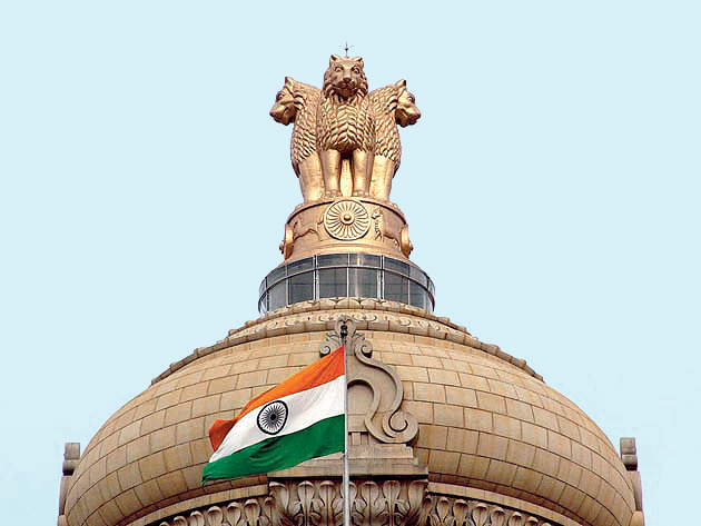 The Indian flag and the State Emblem atop Vidhana Soudha in Bangalore