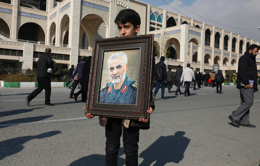 A boy carries a portrait of Iranian Revolutionary Guard Gen. Qassem Soleimani, who was killed in a US airstrike in Iraq, prior to the Friday prayers in Tehran, Iran, on January 3, 2020.