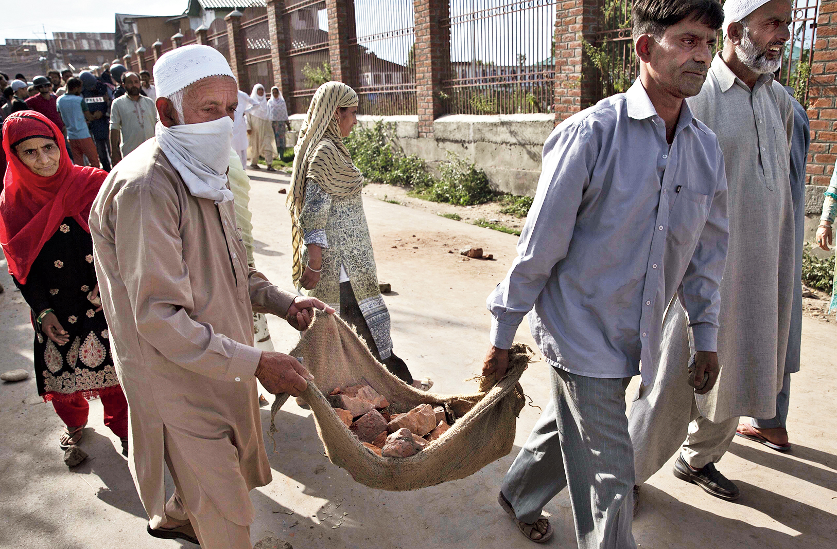 An elderly Kashmiri helps carry stones to throw at security personnel during a protest in Srinagar on Friday.