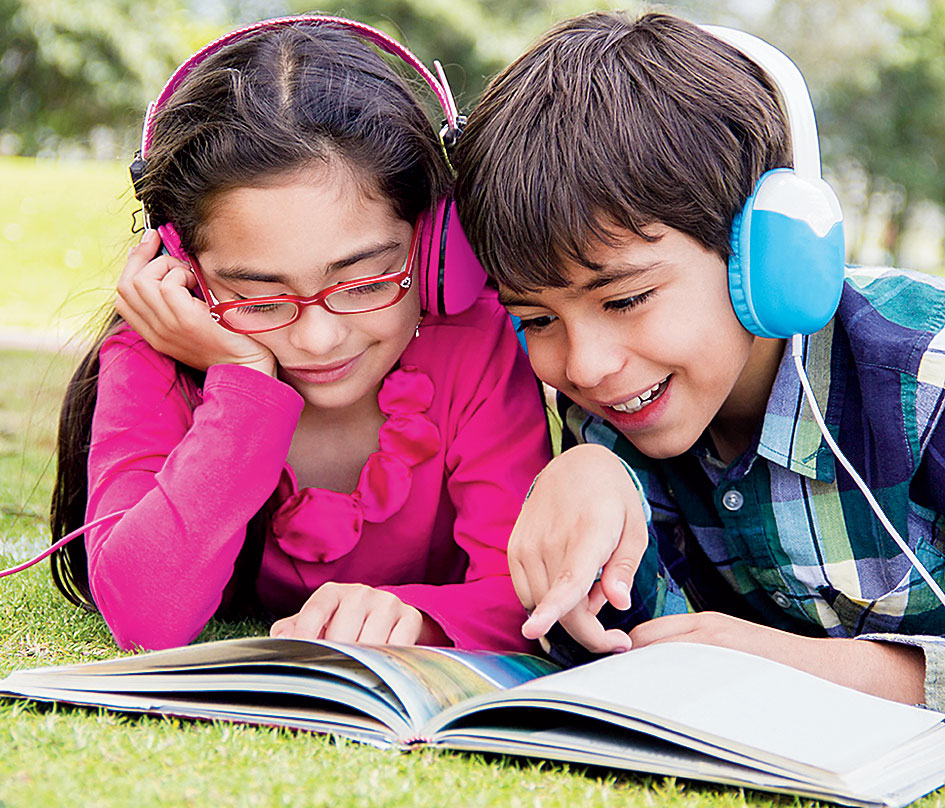 Children read along as they listen to an audiobook