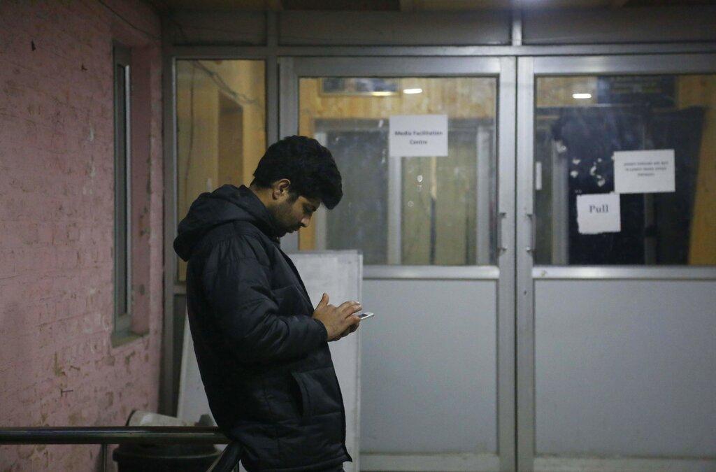 A man checks his cellphone outside a media facilitation centre in Srinagar