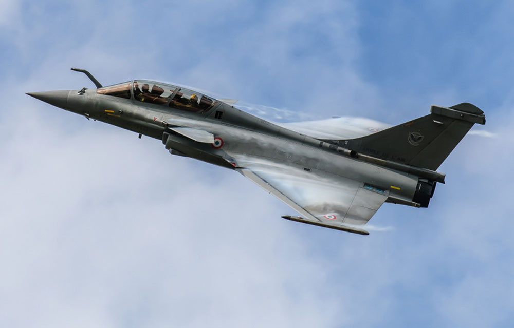 Dassault Rafale flying overhead with vortex over canards and wings in front of clouds
