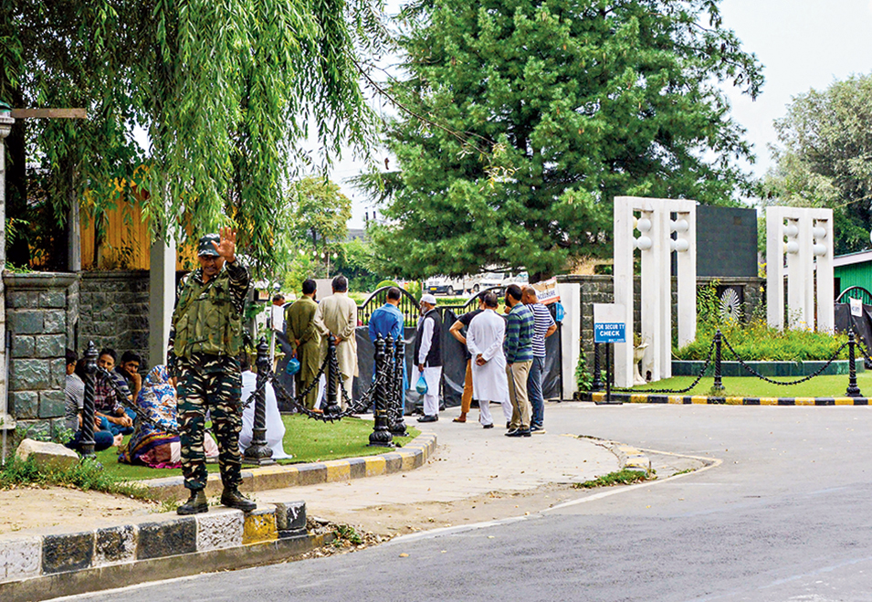 Relatives and supporters of Jammu and Kashmir leaders and former MLAs wait to meet them at SKICC in Srinagar on Monday.